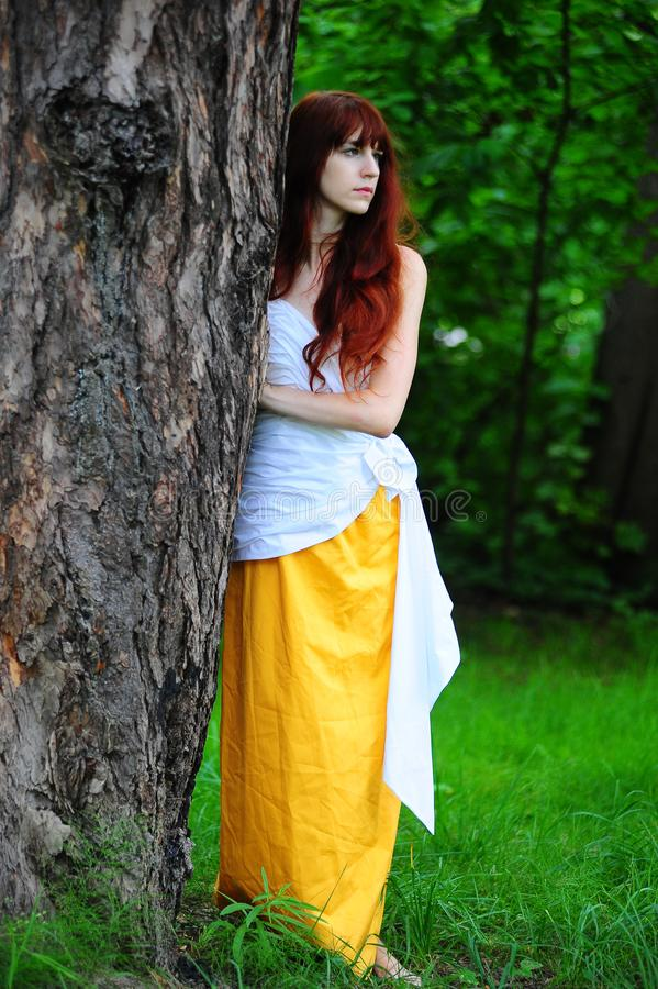 Girl in white with a yellow evening dress by the tree royalty free stock photos