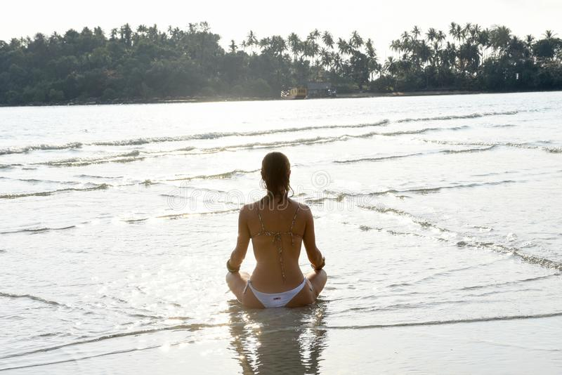 Girl who practices yoga on the beach stock photography