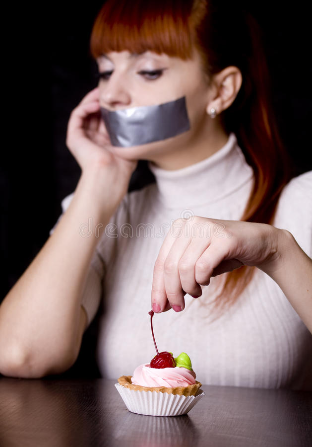 The girl, whose mouth sealed with tape sad looking at cakes. The girl, whose mouth sealed with tape sad looking at cake stock images