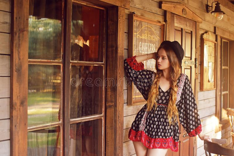 Girl in the Wild West, in Western house. Girl in hat with long cerly hair. Beautiful pretty girl in black hat. Incredible trip, tr stock image