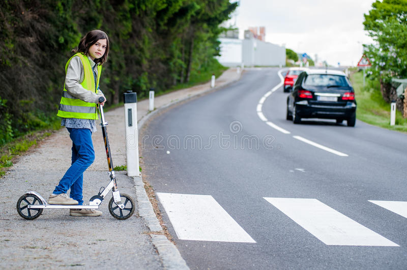 Girl will cross the Street. Young girl with her scooter will go on the crosswalk royalty free stock image