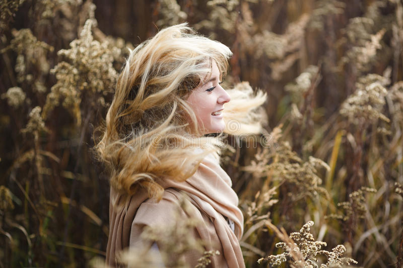 Girl with wind in her hair. Young girl running through the underbrush with wind in her hair, autumn time royalty free stock image
