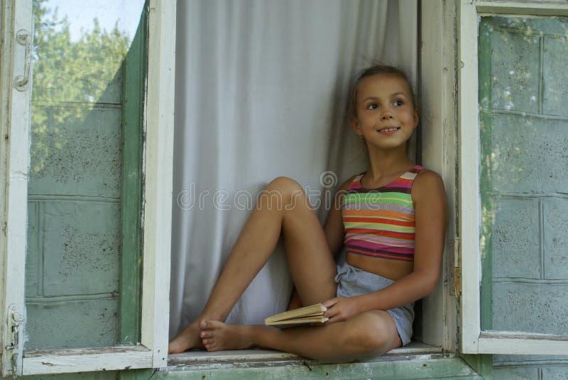 Girl in window stock photo