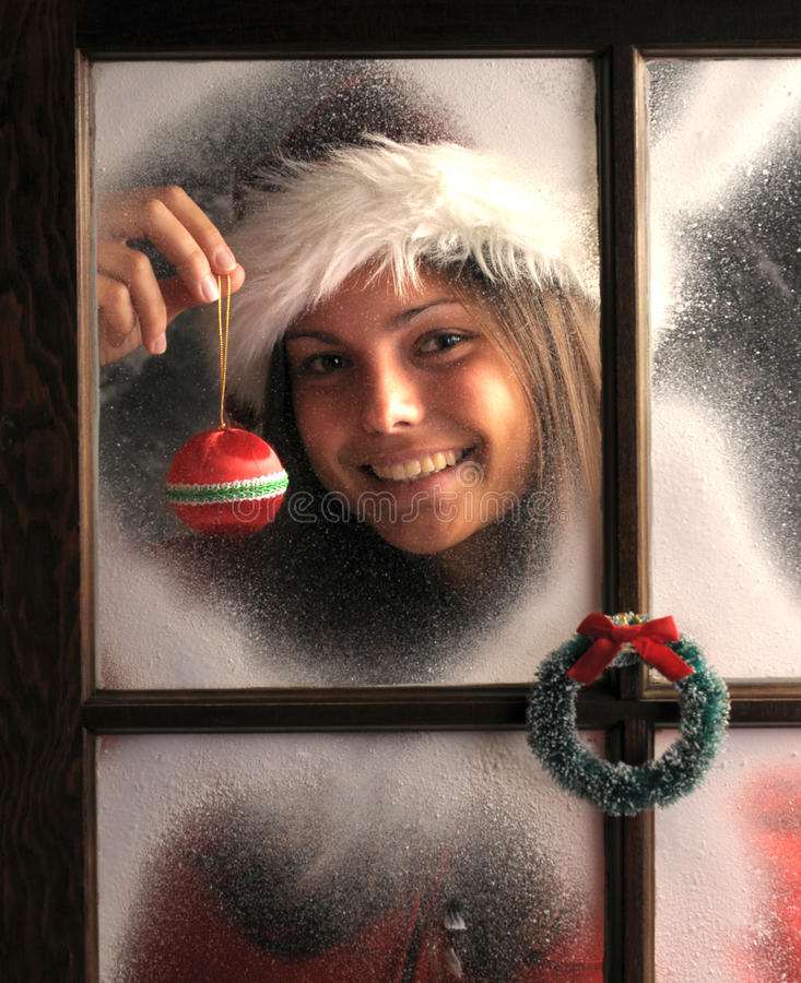 Girl In Window With Christmas Ornament Royalty Free Stock Photos