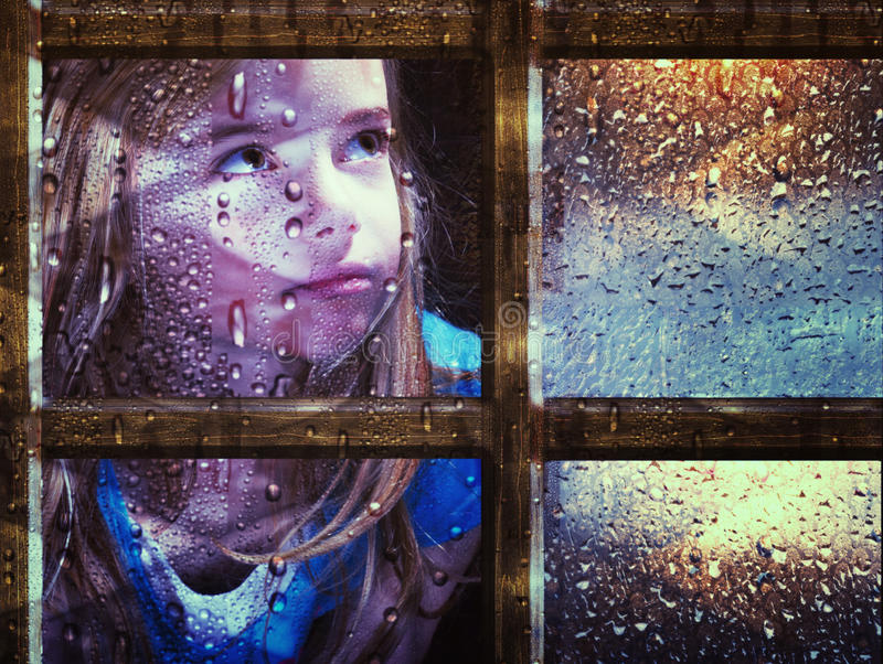 Girl at window in rain. A little girl looking out through a window in the rain stock image