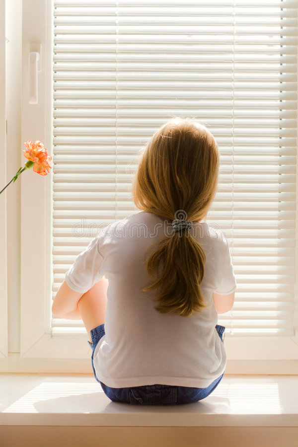 Girl on window-sill. Young blond girl sitting on a window-sill royalty free stock photos