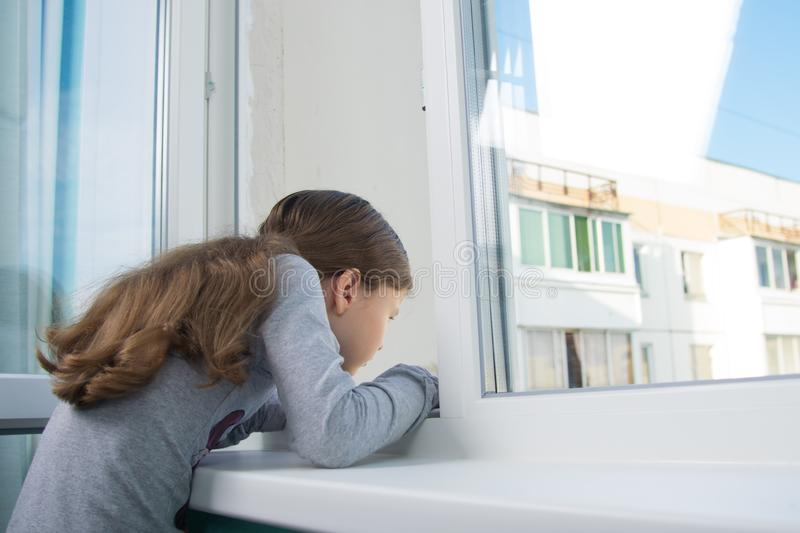 Girl on the windowsill, reaching into the open window stock images