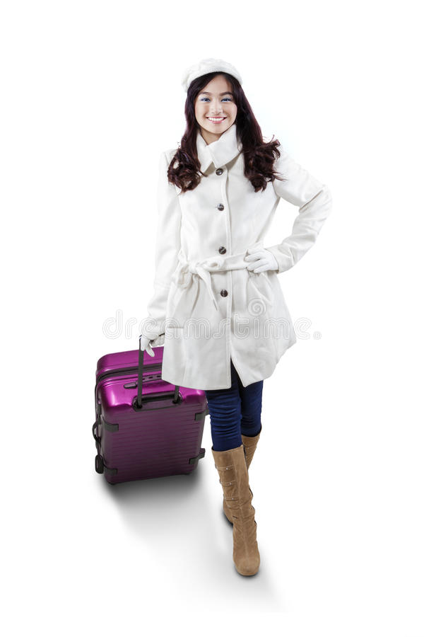 Girl in winter clothes carrying suitcase. Beautiful young girl wearing winter clothes with suitcase for traveling, isolated on white background stock photo