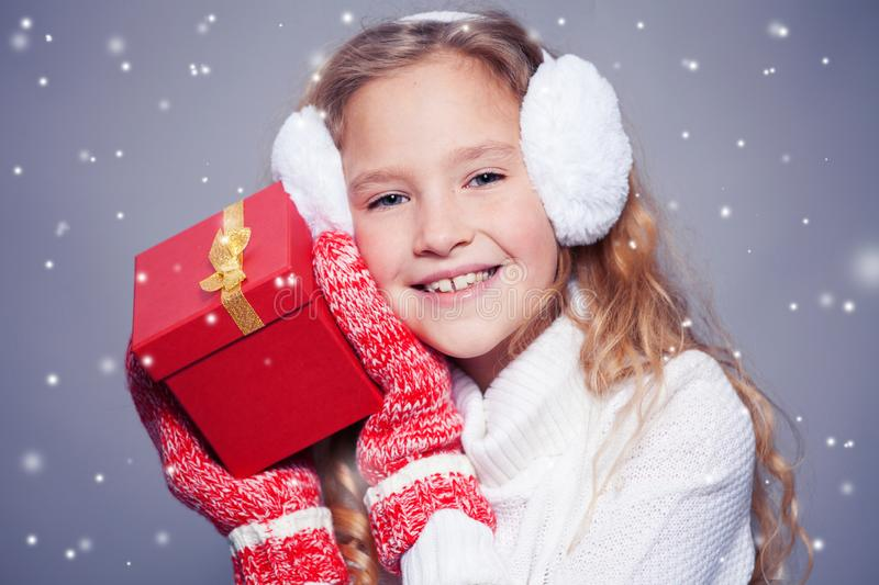Girl in winter clothes with gift. Girl in winter clothes. Happy child with gift. Studio shot stock images