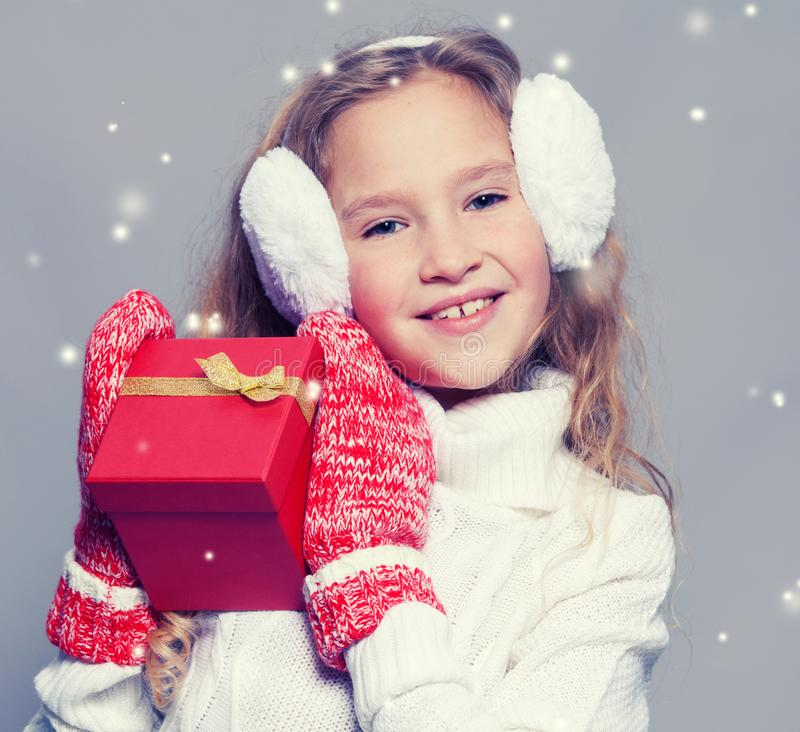 Girl in winter clothes with gift stock images