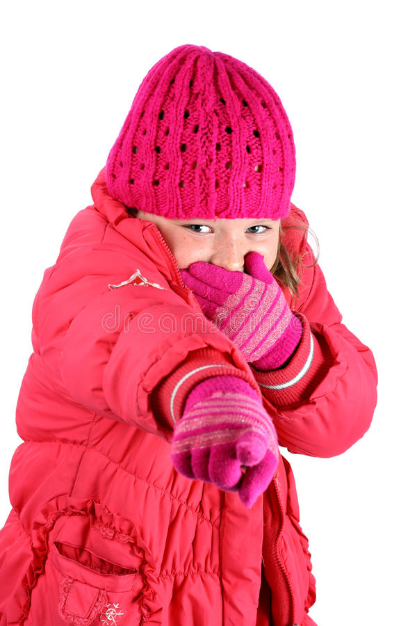 Girl in winter clothes laughing pointing a finger. Portrait of pre-teen girl with pink cap in red winter clothes pointing her finger at camera, laughing stock photo