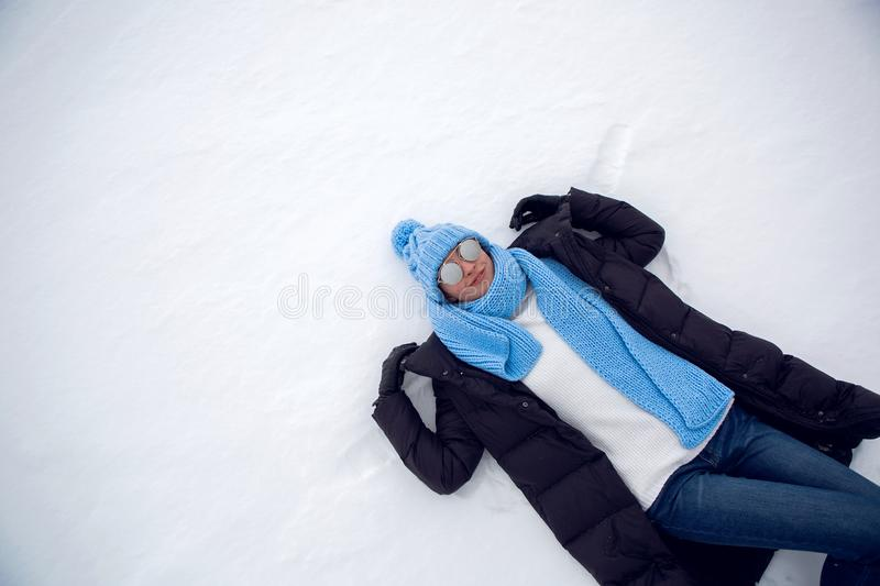 Girl in winter clothes lying stock photos