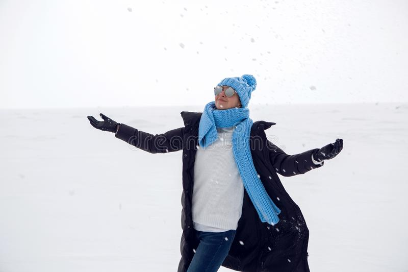 Girl in winter clothes standing on a frozen lake stock images