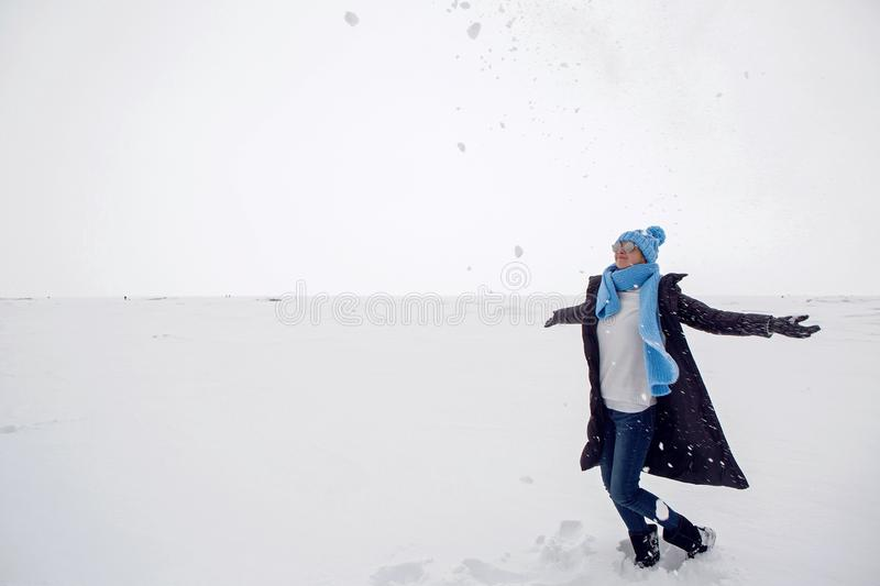 Girl in winter clothes standing on a frozen lake royalty free stock images