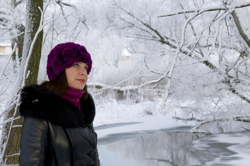 A girl in winter clothes Walking through the snow-covered park. Visible icebound river.  stock photos