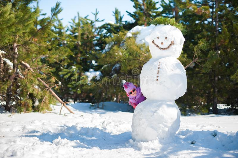 The girl in the winter hiding behind a large snowman. Children in pink jackets and glasses in the sun jumping in the royalty free stock image