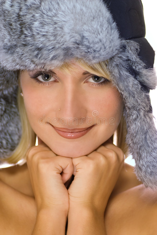 Girl in winter fur-cap. Beautiful young girl in winter fur-cap royalty free stock images