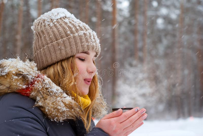Girl blowing on hot tea in winter outdoors royalty free stock photo