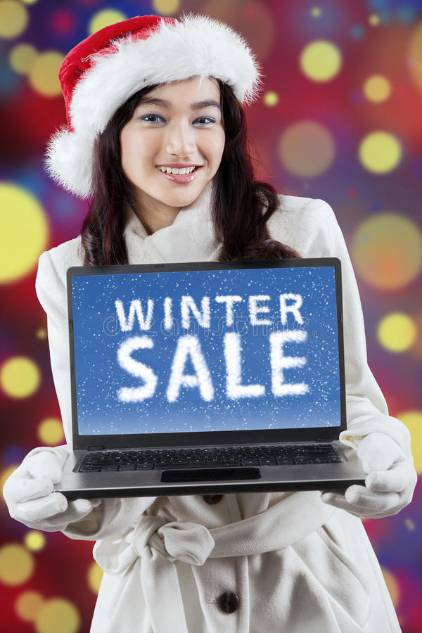 Girl with a winter sale text and bokeh background. Young woman in winter clothes wearing christmas hat and showing a winter sale text on laptop against light royalty free stock images