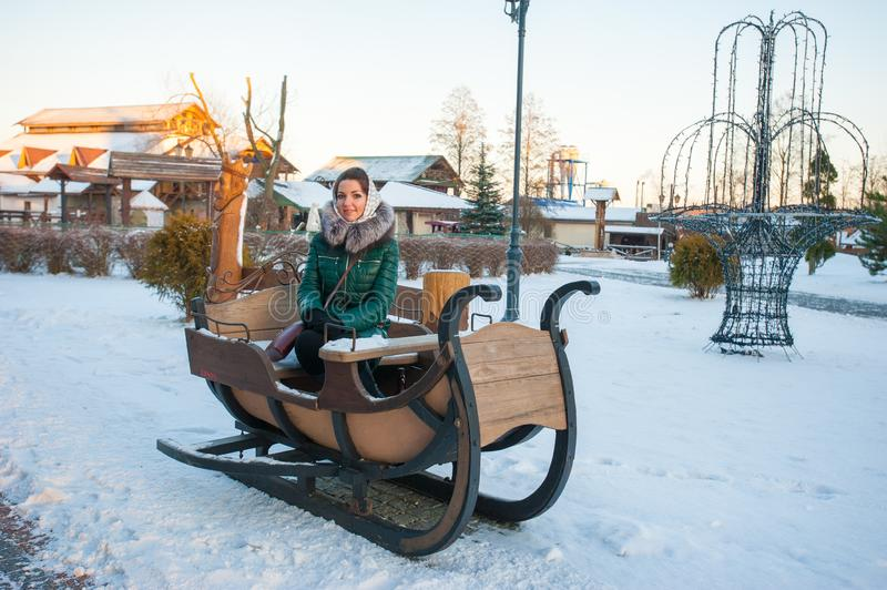 The girl on the winter sled, large sled for skiing. Girl riding a reindeer sleigh royalty free stock image