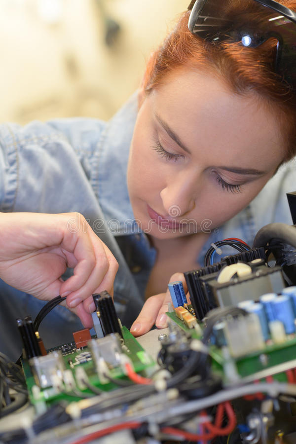 Girl wiorking on printed circuit board stock photography