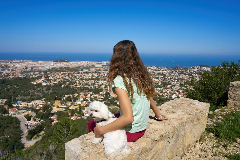 Girl wirh pet dog looking at Denia aerial view. In alicante of Spain stock images