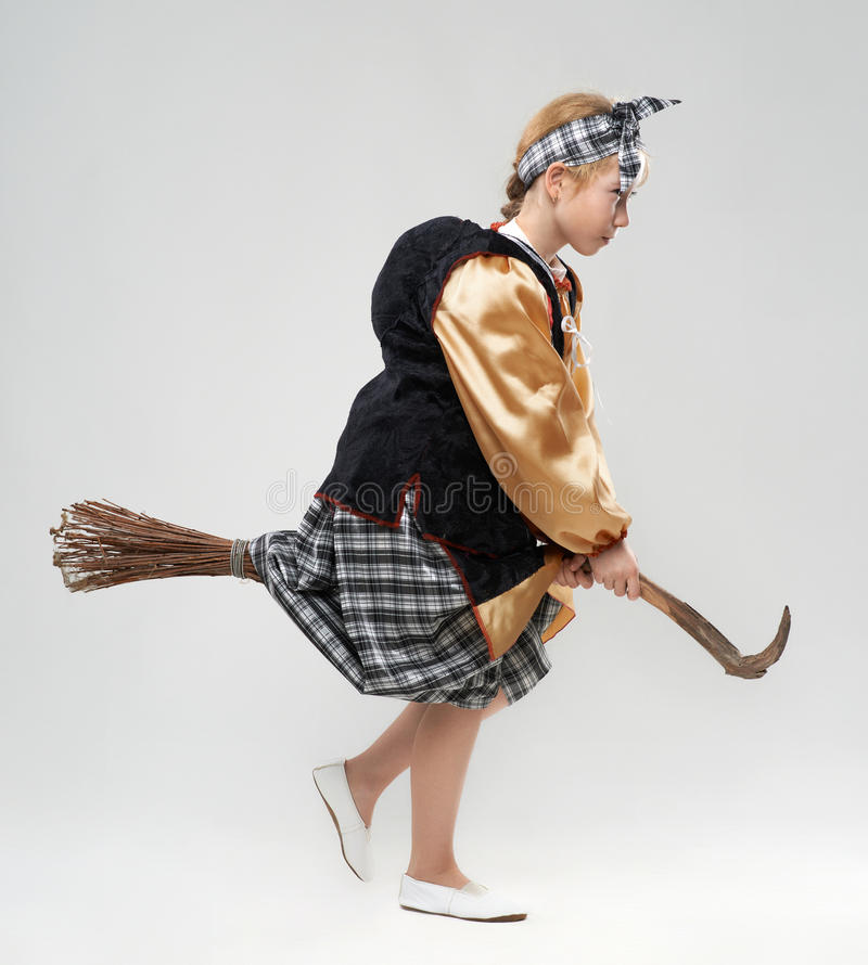 Girl in witch costume flying on a broomstick royalty free stock images
