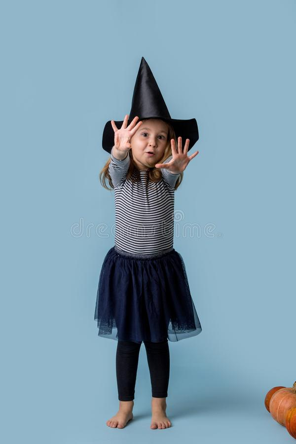 Girl in a witch costume pulls hands and shows fingers royalty free stock photos