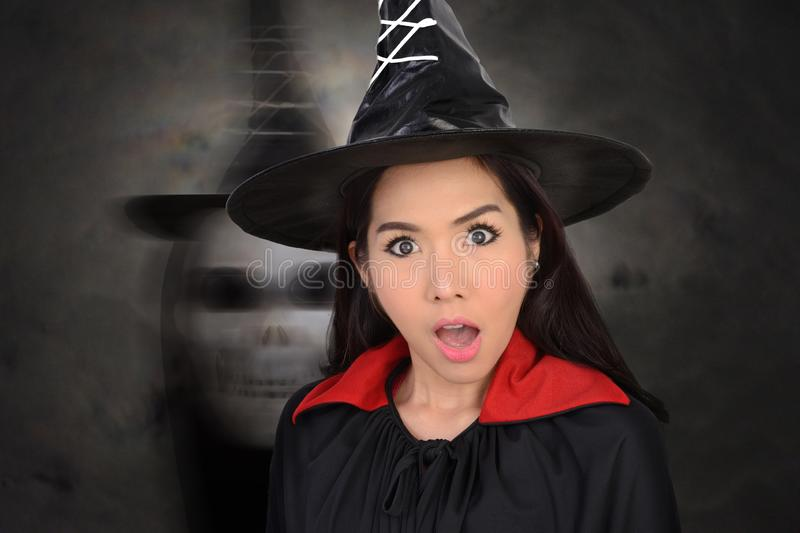 Girl in witch costume was shocked with skull in dark cloud on be. Hind royalty free stock images