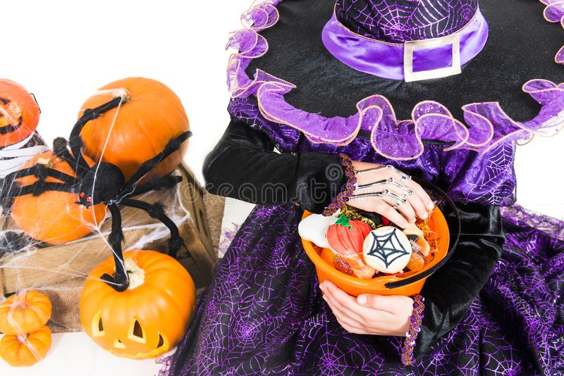 Girl in a Witch Dress with Halloween Accessories and full Bucket royalty free stock image