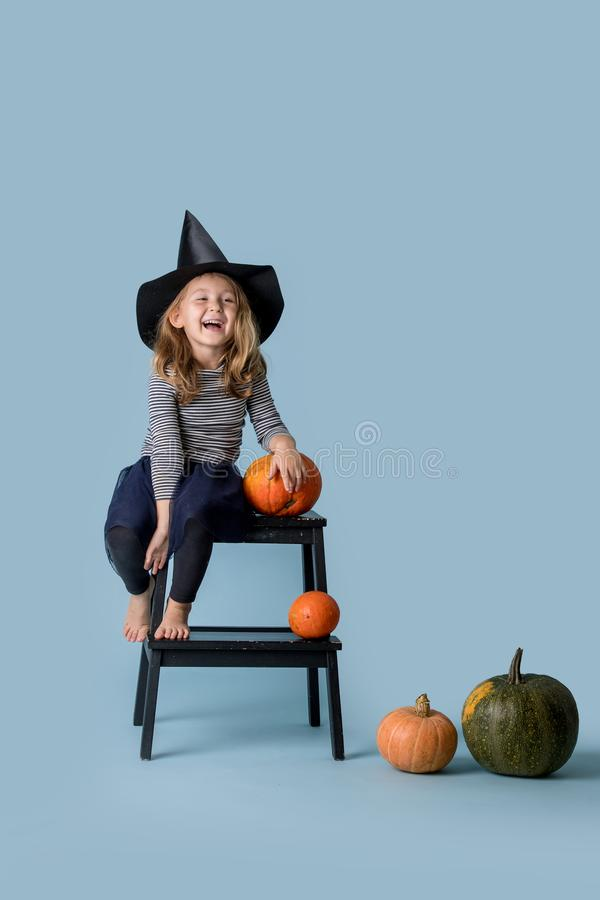 Girl in witch hat and black clothes sits on stepping stool with pumpkin in hand. Little girl in witch hat and black clothing sitting on a side of a stepping stock photo