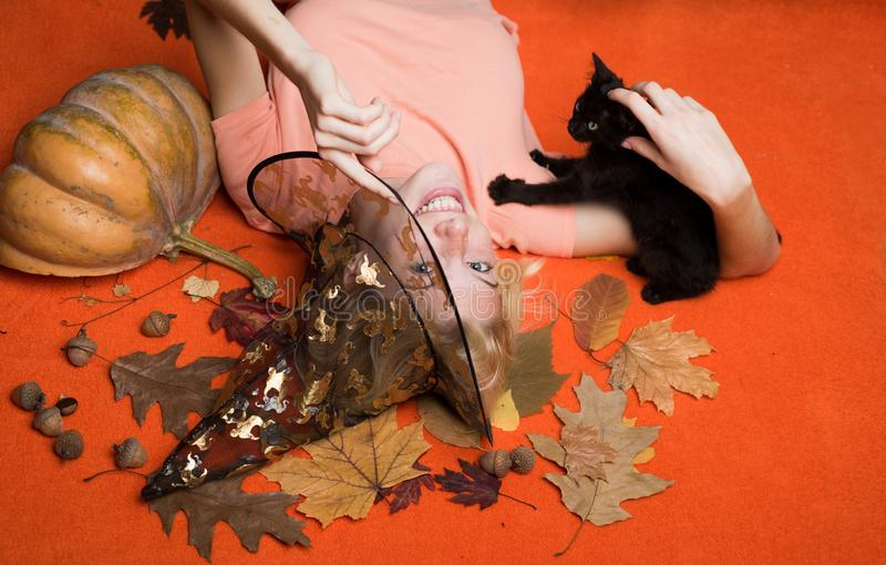 Girl witch plays with black kitten Halloween Witch in black hat. Woman posing with Pumpkin. Pumpkin head jack lantern. Trick or treat royalty free stock image