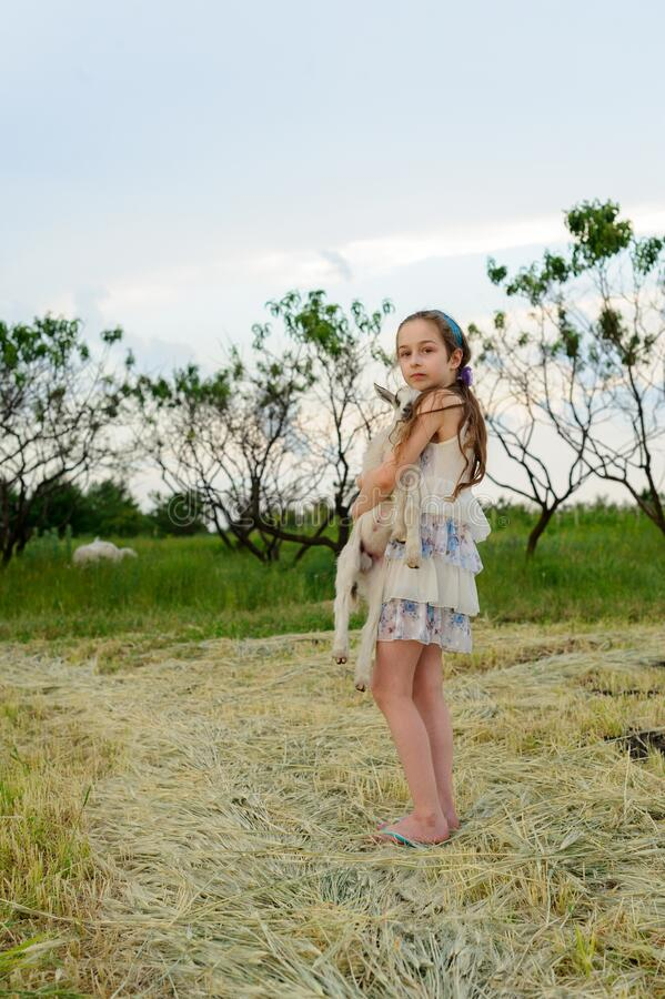 Free Girl With Baby Goat On Farm Outdoors. Village Animals. Happy Child Hugs Goat, Concept Of Unity Of Nature And Man Stock Photos - 171568443