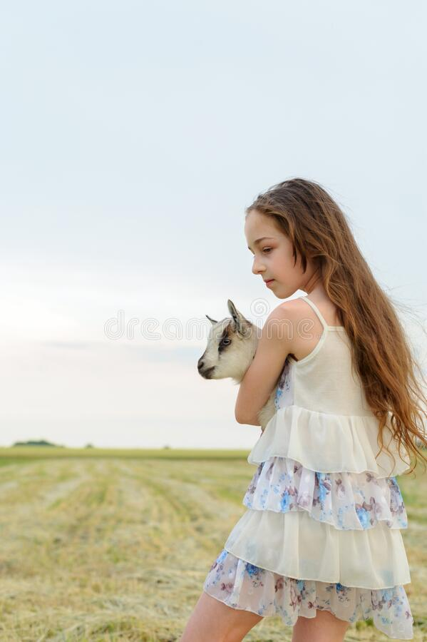 Free Girl With Baby Goat On Farm Outdoors. Village Animals. Happy Child Hugs Goat, Concept Of Unity Of Nature And Man Stock Photo - 171729330
