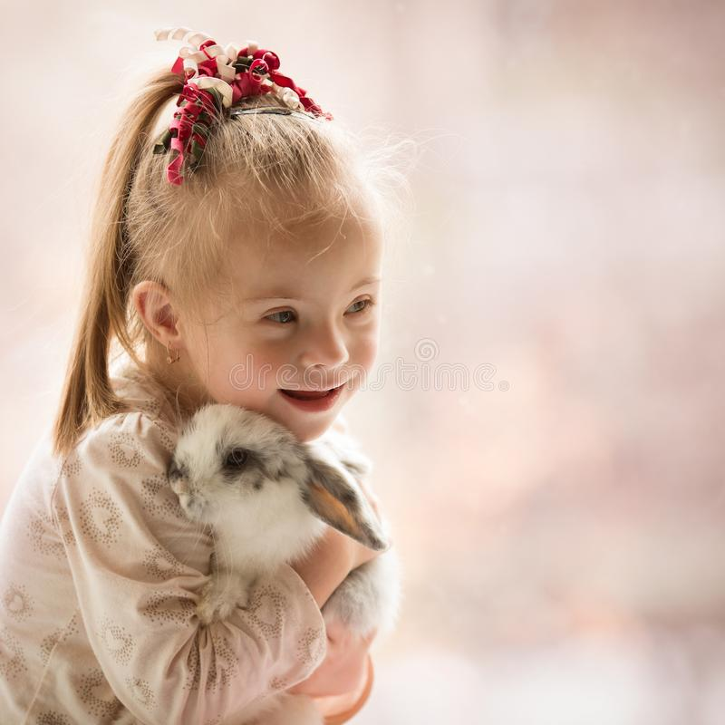 Free Girl With Down Syndrome Hugs Rabbit Royalty Free Stock Photo - 102887405