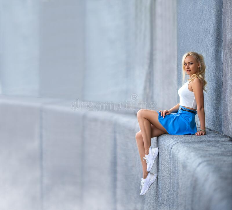 Free Girl With Perfect Legs In Sneakers Sitting On The Parapet Of High Building Stock Image - 174645901