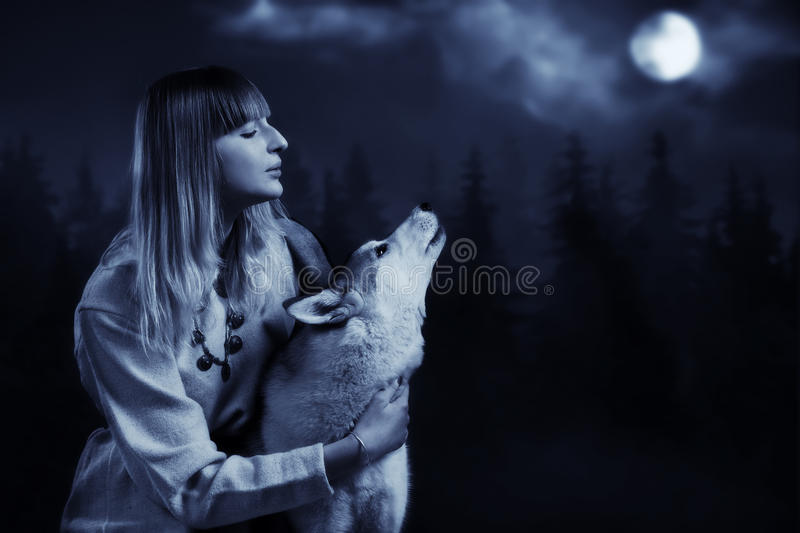 Girl and wolf in the deep forest stock photo