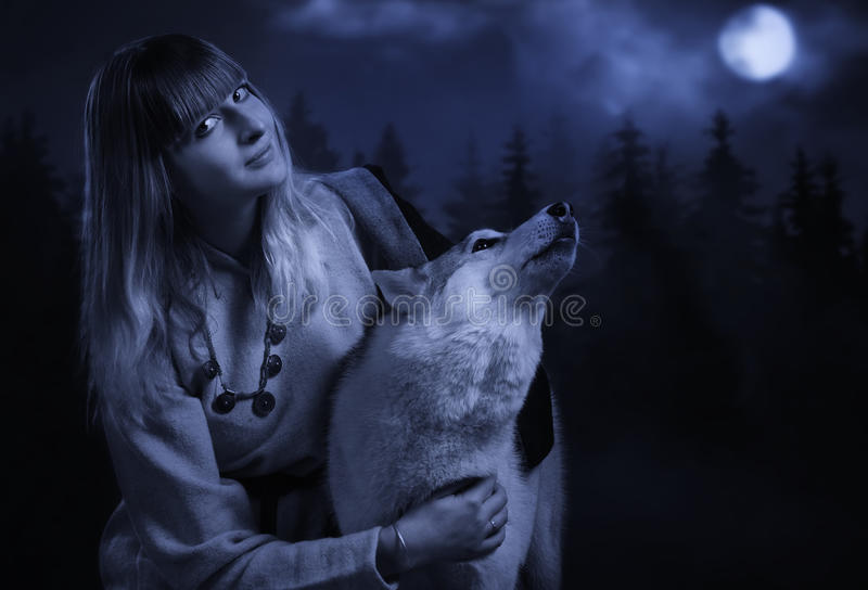 Girl and wolf in the deep forest. Slavonian girl in the traditional suit and gey wolf in the deep forest royalty free stock photos