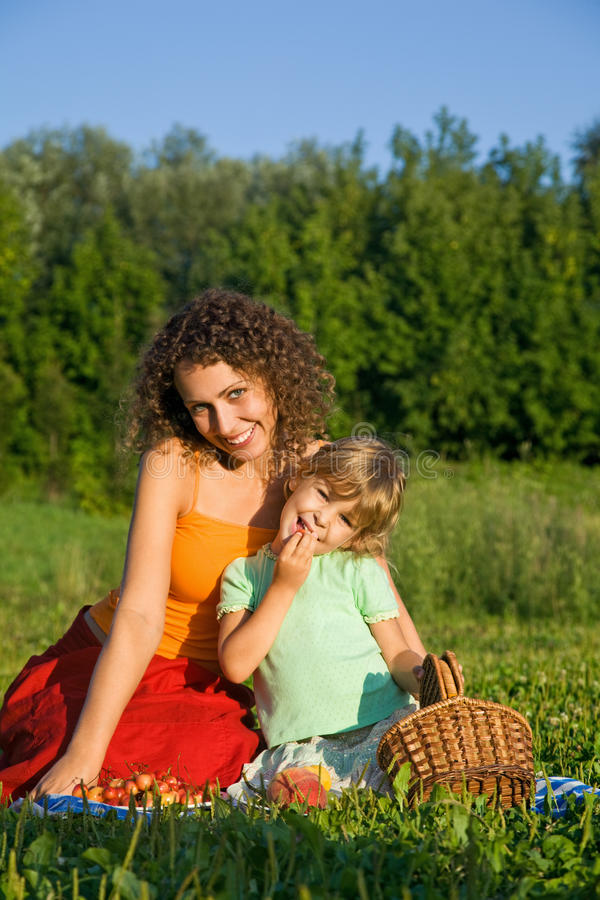 Girl and Women eats sweet cherries on picnic stock images