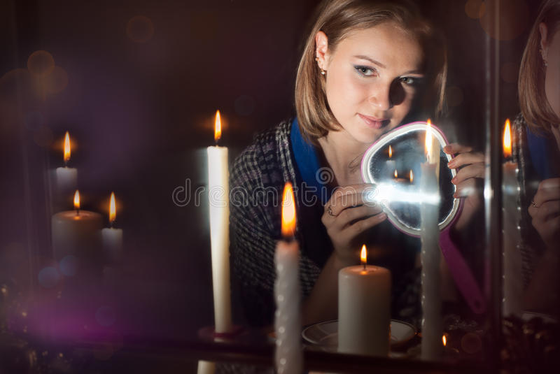 The girl wonders with a mirror. In a dark room stock image