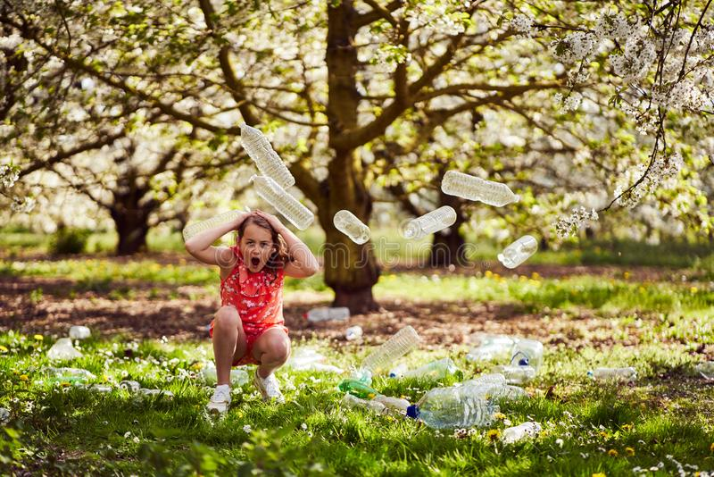 Girl in a wood with plastic bottles to create awareness. Young girl cowering in a wood surrounded by plastic bottles and showing awareness fear of damage to the stock images