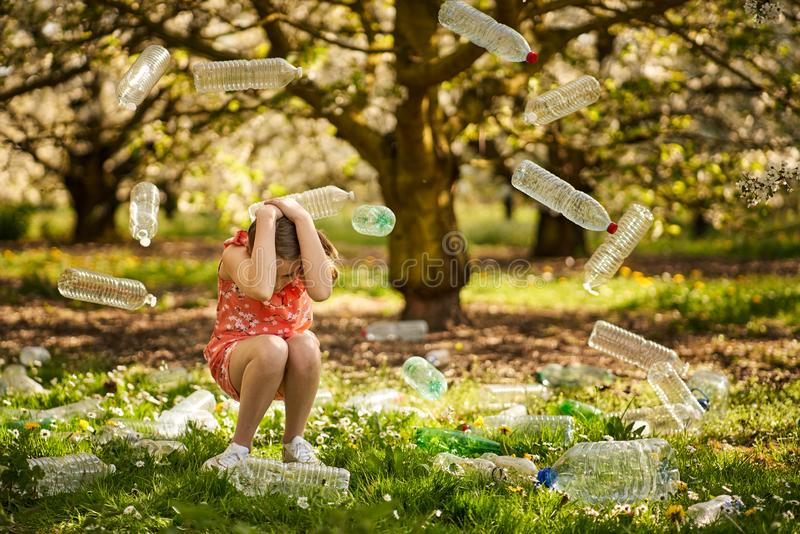 Girl in a wood with plastic bottles. Young girl cowering in a wood surrounded by plastic bottles and showing awareness (fear) of damage to the planet by overuse royalty free stock image