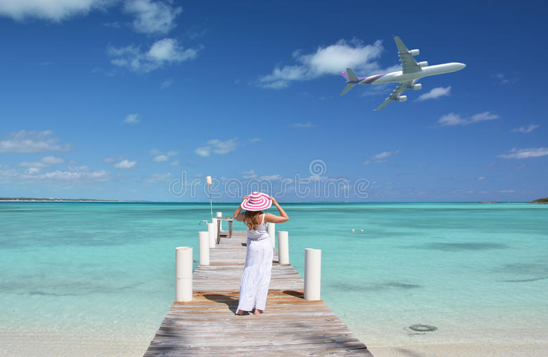 Girl on the wooden jetty looking to the ocean royalty free stock image