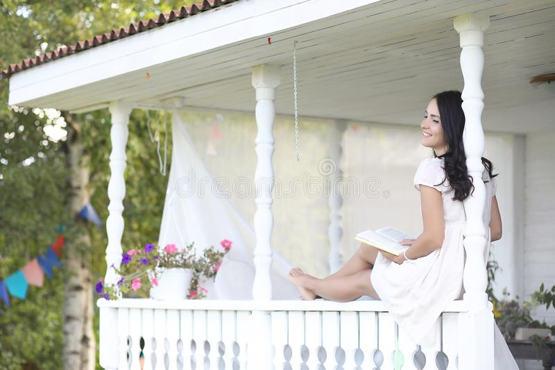 Girl on the wooden porch near the house stock image