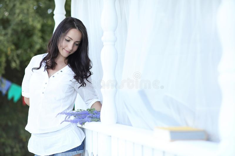 Girl on the wooden porch near the house stock images