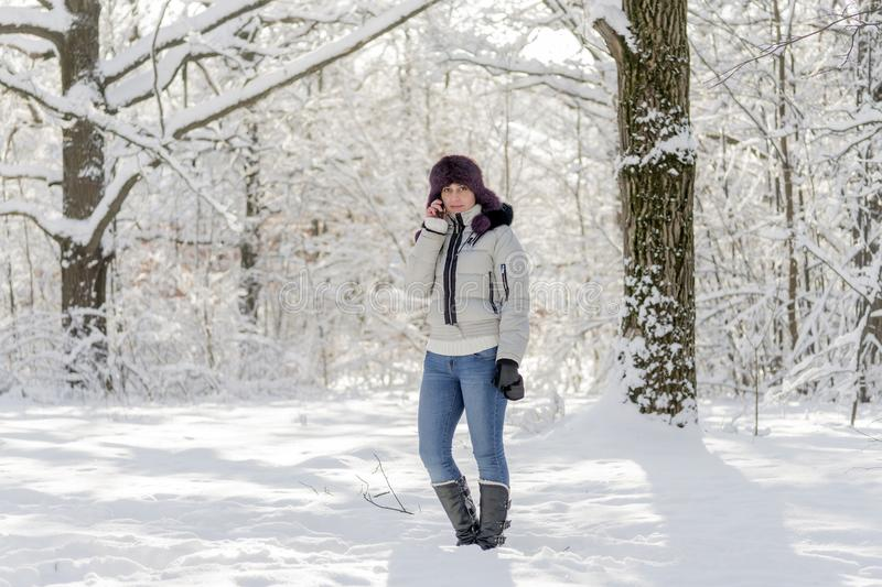 Girl in the woods talking on the phone. Winter, day. Girl in the woods talking on the phone. Winter royalty free stock image