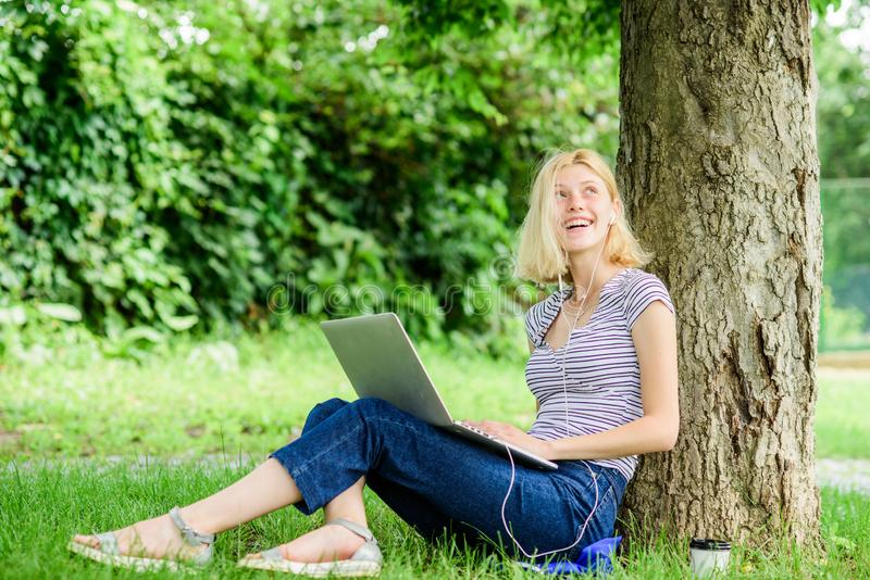 Girl work with laptop in park. Reasons why you should take your work outside. Nature is essential to wellbeing and stock photography