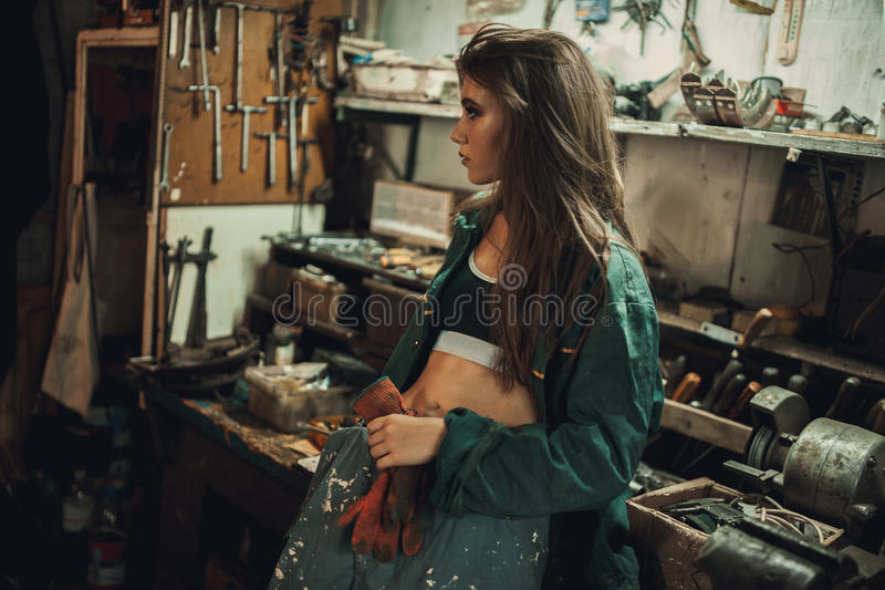 Girl worker in dirty overalls stands in workshop among tools. stock photography