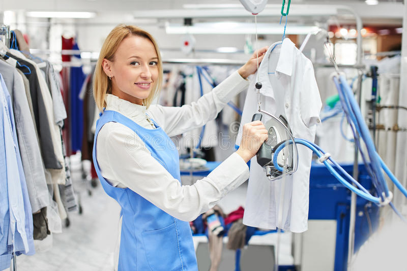 Girl worker Laundry ironed clothes. And smiling at the dry cleaners royalty free stock images