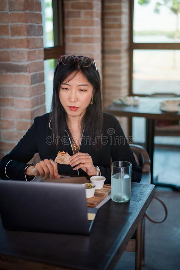 Girl working and having a meal. Girl working on laptop and having a quick snack woman bar cafe eat eating toast bite restaurant freelance fast lunch break royalty free stock photography